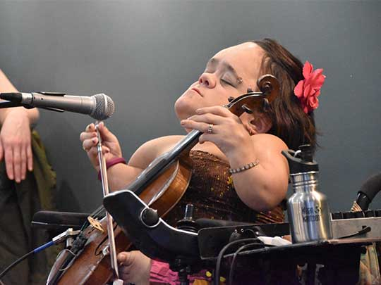 Musician Gaelynn Lea playing the violin and singing